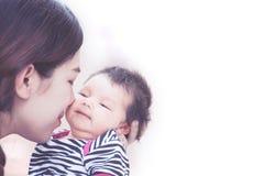 Junge asiatische Mutter, die ihr neugeborenes Baby umarmt und küsst Stockfoto