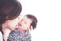 Junge asiatische Mutter, die ihr neugeborenes Baby umarmt und küsst Lizenzfreies Stockfoto
