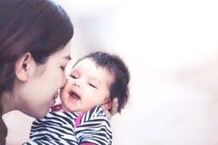 Junge asiatische Mutter, die ihr neugeborenes Baby umarmt und küsst Lizenzfreie Stockfotografie