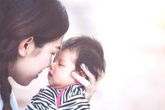 Junge asiatische Mutter, die ihr neugeborenes Baby umarmt und küsst Stockbild