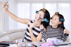 Junge asiatische Mutter und Tochter mit Haarlockenwicklern nehmen selfie im Schlafzimmer stockfoto