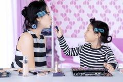 Junge asiatische Mutter und Tochter mit Haarlockenwicklern spielen mit Lippenstift im Schlafzimmer lizenzfreie stockfotografie