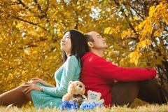 Junge asiatische Paare in der Liebe und im Haben des Herbstspaßes Lizenzfreies Stockfoto