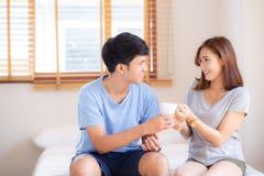 Junge asiatische Paare des schönen Porträts geben einen Tasse Kaffee mit zusammen lächeln und glückliche lizenzfreie stockfotos