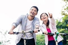 Junge asiatische Paare, die zusammen lachen, während das Reiten radfährt Stockbilder