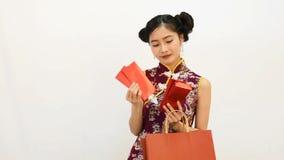 Junge asiatische Schönheitsfrau tragendes cheongsam und Finden des roten Pakets des Geldes in ihrer Einkaufstasche für chinesisch stock video