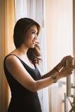 Junge asiatische sexy Frau, die im schwarzen Kleid steht Lizenzfreies Stockbild