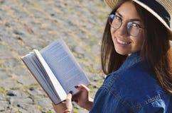 Junge asiatische Studentin liest ein Buch auf der Bahn lizenzfreie stockfotos