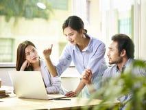 Junge asiatische Unternehmensleiter, die im Büro sich treffen Lizenzfreie Stockfotos