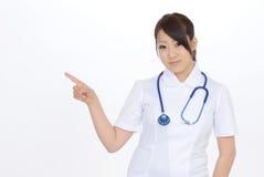 Junge asiatische weibliche Krankenschwester, die leeres Zeichen zeigt Stockbild