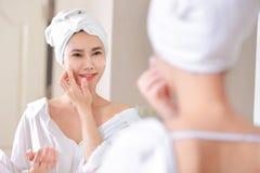 Junge Asien-Frau, die Grundlage oder Feuchtigkeitscreme auf ihrem Gesicht anwendet Stockbilder