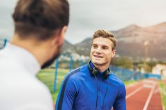 Junge Athleten, die einen Lauf auf Leichtathletikbahn üben stockbild