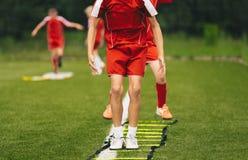 Junge Athleten, die mit Fußball-Ausrüstung ausbilden Fußball-Geschwindigkeits-Training mit Leiter stockfotos