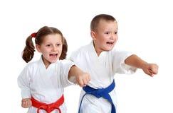 Junge Athleten im Kimono schlugen einen Durchschlagsarm auf einem weißen Hintergrund stockbilder