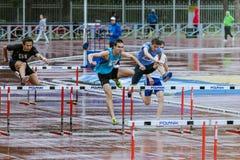 Junge Athleten lassen die 110-Meter-Hürden im Regen laufen Lizenzfreies Stockfoto