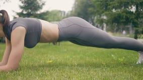 Junge Athletenfrau, die Plankenübung im Sommerpark während Turnhallentraining tut