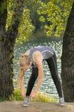 Junge athletische Blondine, die draußen Sportschnürsenkel binden Stockfotografie