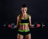 Junge athletische Frau in der Sportkleidung mit Dummköpfen im Studio gegen schwarzen Hintergrund Ideale weibliche Sportzahl Stockfotos