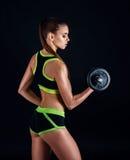 Junge athletische Frau in der Sportkleidung mit Dummköpfen im Studio gegen schwarzen Hintergrund Ideale weibliche Sportzahl Stockbild