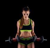 Junge athletische Frau in der Sportkleidung mit Dummköpfen im Studio gegen schwarzen Hintergrund Ideale weibliche Sportzahl Stockbilder