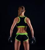 Junge athletische Frau in der Sportkleidung mit Dummköpfen im Studio gegen schwarzen Hintergrund Ideale weibliche Sportzahl Eignu Stockfotos