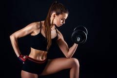 Junge athletische Frau in der Sportkleidung mit Dummköpfen im Studio gegen schwarzen Hintergrund Ideale weibliche Sportzahl Stockfoto