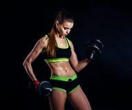 Junge athletische Frau in der Sportkleidung mit Dummköpfen im Studio gegen schwarzen Hintergrund Ideale weibliche Sportzahl lizenzfreie stockfotografie
