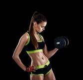 Junge athletische Frau in der Sportkleidung mit Dummköpfen im Studio gegen schwarzen Hintergrund Ideale weibliche Sportzahl stockfotografie