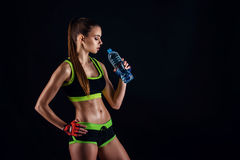 Junge athletische Frau in der Sportkleidung mit einer Flasche im Studio gegen schwarzen Hintergrund Ideale weibliche Sportzahl Lizenzfreies Stockbild