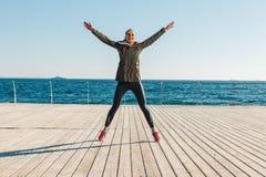 Junge athletische Frau, die auf den Strand springt Lizenzfreie Stockbilder