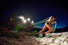 Junge athletische Frau, die Auto im Winter zieht stockbilder