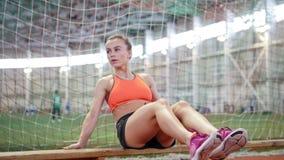 Junge athletische Frau, die ihre ABS unter Verwendung einer Bank ausbildet stock video
