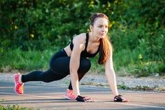 Junge athletische Frau, die sich vorbereitet, am Park zu laufen, draußen Konzept eines gesunden Lebensstils stockfotografie