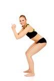 Junge athletische Frau führt Hocken durch Stockbild