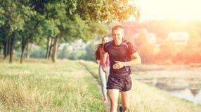 Junge athletische Leute, die nahen Teich im Freien rütteln Stockbild