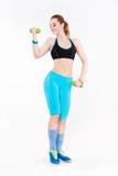 Junge athletische rothaarige Frau in der Sportkleidung, die Übung mit Dummköpfen tut Lizenzfreie Stockfotos