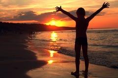 Junge atmet bei dem brennenden Sonnenuntergang auf dem Meer tief ein stockfoto