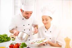 Junge attractives Fachleutechefs, die zusammen kochen lizenzfreie stockbilder