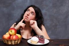 Junge attraktive überladene Frau, die zwischen gesundem Lebensmittel wählt lizenzfreie stockfotos