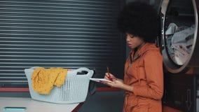 Junge attraktive Afroamerikanerfrauen, die ?schreiben, um Liste ?auf dem Notizblock zu tun sitzt in der allgemeinen W?scherei der stock video footage