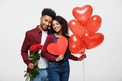 Junge attraktive Afroamerikanerpaare auf Datierung mit Rotrose, -herzen und -ballon stockbild
