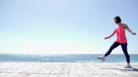 Junge attraktive athletische Frau tut Wagenrad auf der Strandtragenden Rosa- und violettenausstattung Langsame Bewegung stock video footage