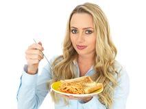 Junge attraktive blonde behaarte Frau, die eine Platte von Spaghettis auf Toast isst Lizenzfreies Stockfoto