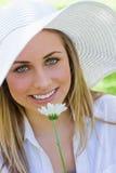 Junge attraktive blonde Frau beim Anhalten einer weißen Blume Stockbild