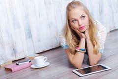 Junge attraktive blonde Frau benutzt Tablette vor weißer hölzerner Wand Lizenzfreies Stockfoto