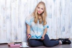 Junge attraktive blonde Frau benutzt Tablette vor weißer hölzerner Wand Lizenzfreie Stockfotografie