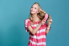 Junge attraktive blonde Frau, die ihr Haar mit rosa Kamm auf blauem Hintergrund bürstet Lizenzfreies Stockfoto
