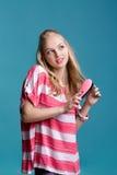 Junge attraktive blonde Frau, die ihr Haar mit rosa Kamm auf blauem Hintergrund bürstet Stockbilder