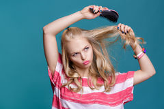Junge attraktive blonde Frau, die ihr Haar mit rosa Kamm auf blauem Hintergrund bürstet Lizenzfreie Stockfotos