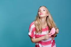Junge attraktive blonde Frau, die ihr Haar mit rosa Kamm auf blauem Hintergrund bürstet Lizenzfreie Stockfotografie